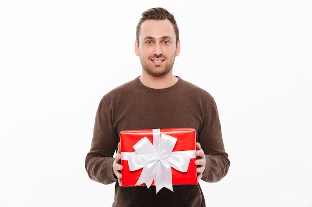 Sorpresa felice del contenitore di regalo della tenuta del giovane.