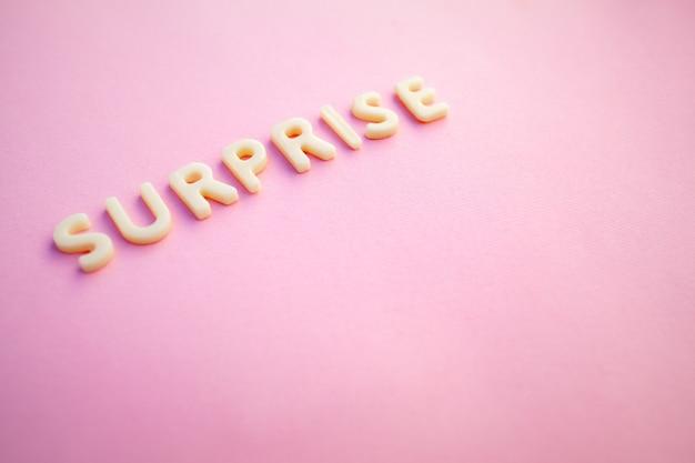 Sorpresa la parola scritta in lettere bianche voluminose su un bellissimo sfondo rosa.