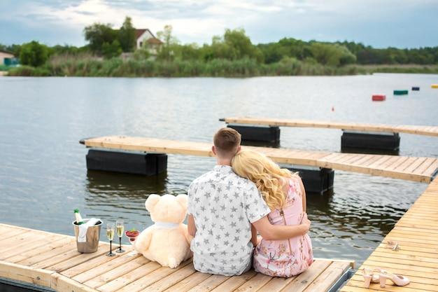 Sorpresa per un appuntamento romantico. un giovane ragazzo e una ragazza su un molo di legno. abbraccia e bacia mentre sei seduto sul molo. storia d'amore romantica