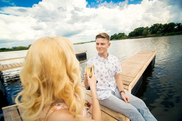 Sorpresa per un appuntamento romantico. un giovane ragazzo e una ragazza su un molo di legno. alza i bicchieri con lo champagne.