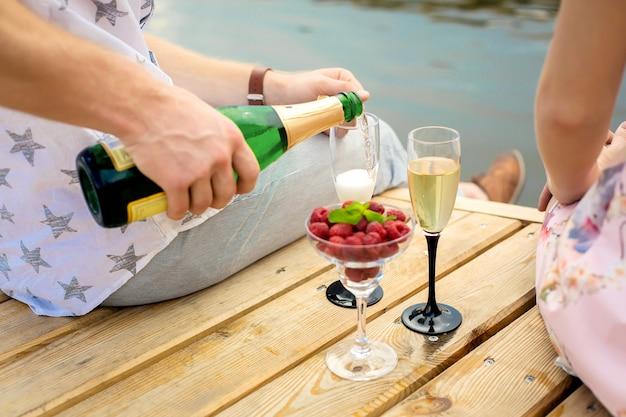 Sorpresa per un appuntamento romantico. un giovane ragazzo e una ragazza su un molo di legno. il ragazzo versa lo champagne nei bicchieri.