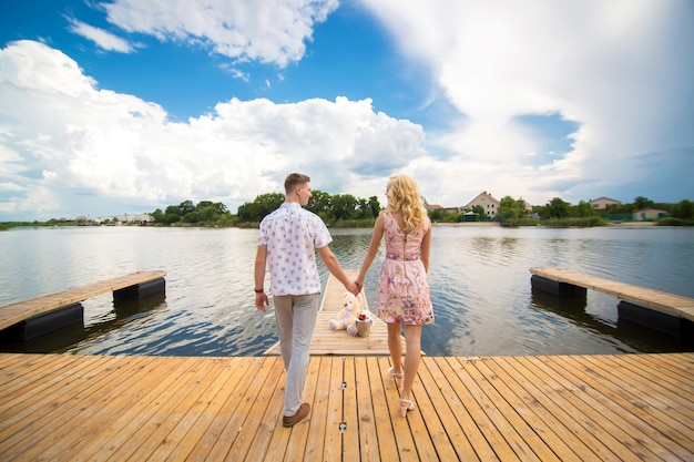 Sorpresa per un appuntamento romantico. un ragazzo e una ragazza su un molo che si affaccia sul lago. il ragazzo dà alla ragazza un orsacchiotto.