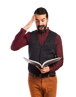 Sorpresa uomo che indossa il libro di lettura del panciotto