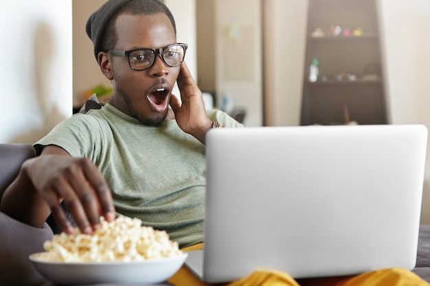 Sorpreso giovane uomo che indossa occhiali da vista e cappello trascorrere la serata a casa utilizzando il computer portatile