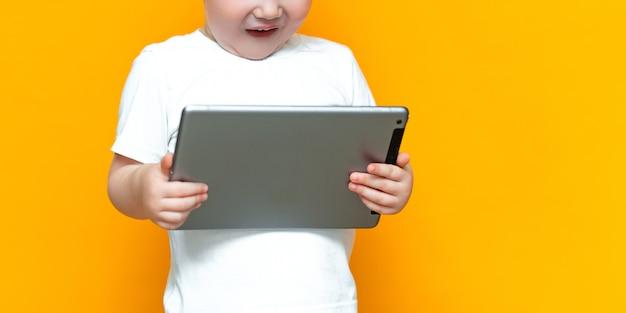 Sorpreso ragazzo biondo di tre anni con la bocca aperta sorpreso, con in mano un tablet pc e guardando la telecamera
