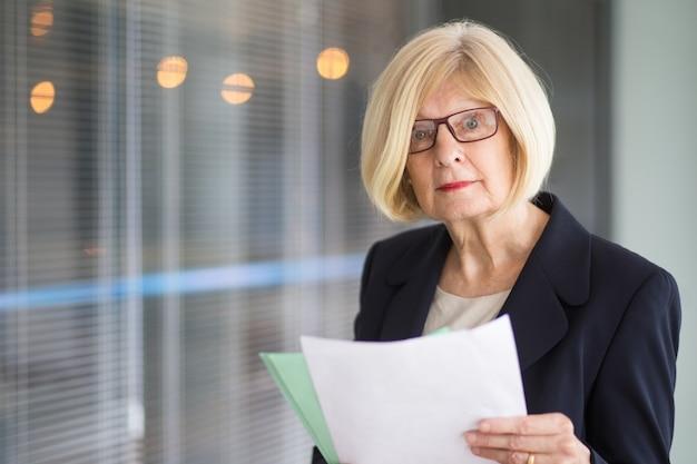 Sorpreso senior business lady holding documenti