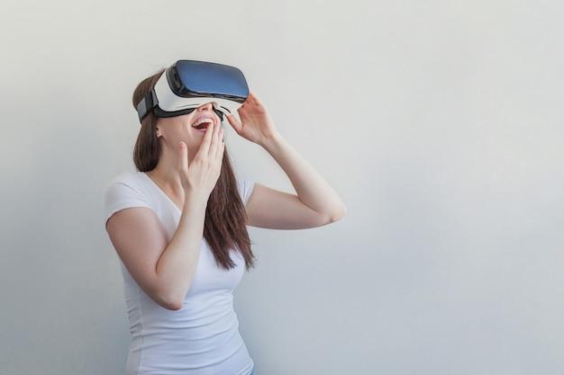 Sorrida la giovane donna che indossa usando la cuffia avricolare del casco di vetro di realtà virtuale vr su bianco