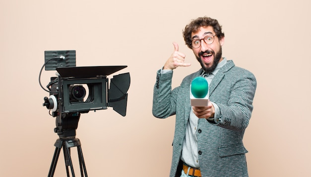 Sorridendo allegramente e indicando la fotocamera mentre ti fai una telefonata in seguito gesto, parlando al telefono
