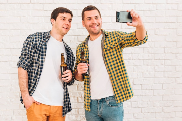 Sorridendo due amici maschii che tengono bottiglia di birra che prende selfie sul telefono cellulare