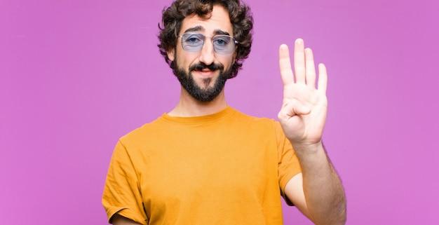 Sorridendo e guardando amichevole, mostrando il numero quattro o il quarto con la mano in avanti, conto alla rovescia
