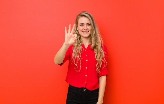 Sorridendo e guardando amichevole, mostrando il numero tre o terzo con la mano in avanti, conto alla rovescia