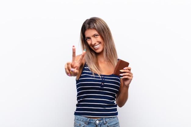 Sorridendo e sembrando felice, spensierato e positivo, gesticolando vittoria o pace con una mano
