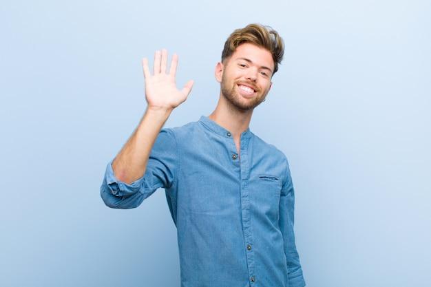 Sorridendo felicemente e allegramente, agitando la mano, dandoti il benvenuto e salutandoti, o salutandoti