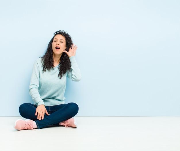 Sorridendo, guardando con curiosità di lato, cercando di ascoltare pettegolezzi o di sentire un segreto