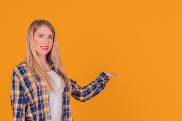 Sorridendo una giovane donna che presenta qualcosa contro uno sfondo arancione