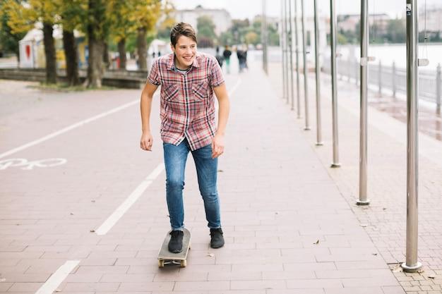 Sorridente adolescente equitazione skateboard vicino pista ciclabile