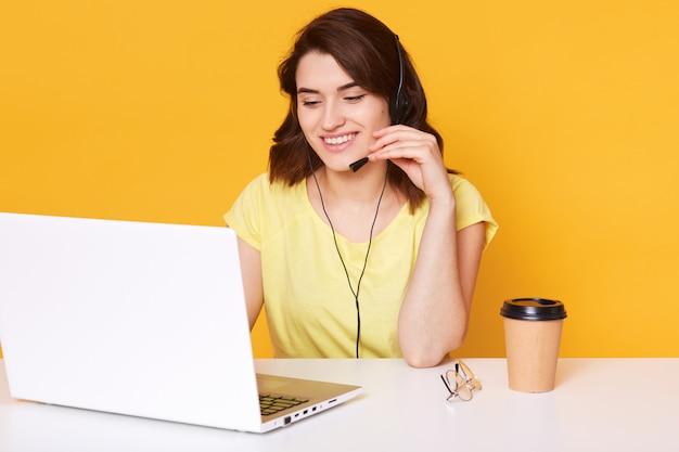 Sorridente allegro supporto telefono operatore donna in cuffia ha una conversazione con il suo cliente, isolato su giallo