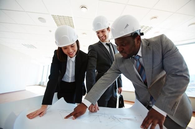 Sorridente architetti guardando blueprint