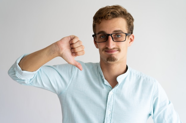 Sorridente bel ragazzo con gli occhiali che esprimono disapprovazione.