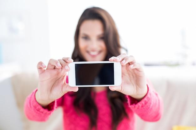 Sorridente bella bruna rilassante sul divano e prendendo selfie