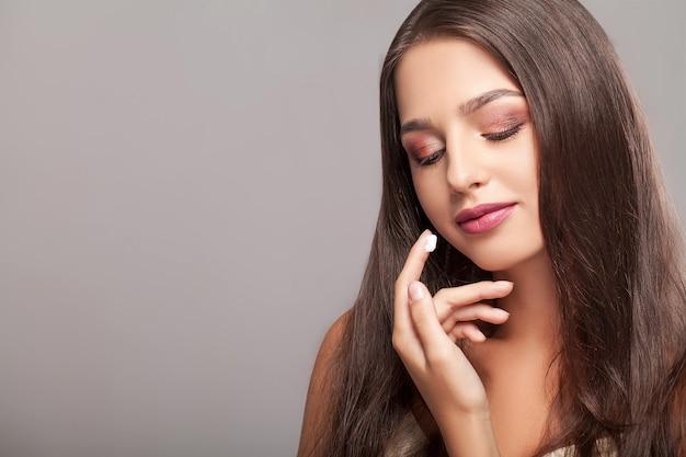 Sorridente bella donna applicando la crema sul viso