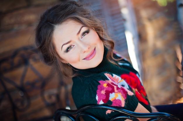 Sorridente bella donna in un maglione nero