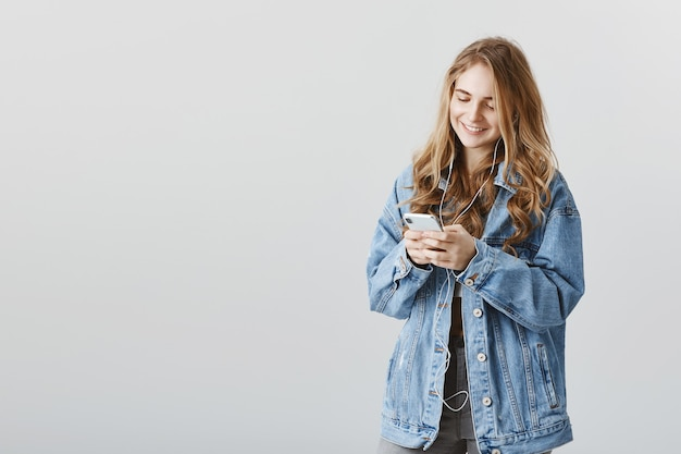 Sorridente bella ragazza bionda utilizzando il telefono cellulare, ascoltando musica in cuffia