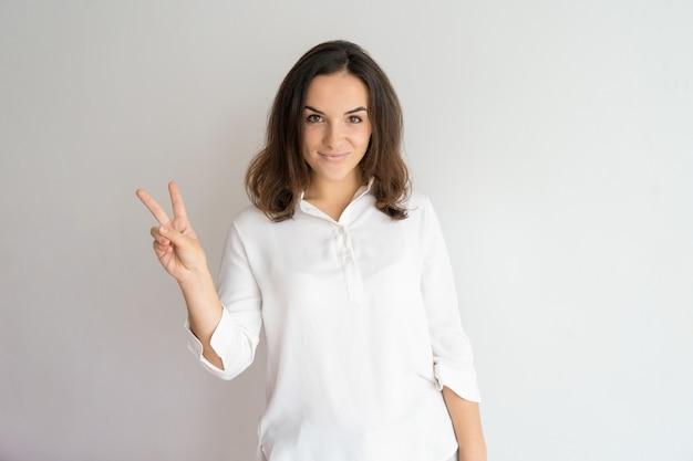 Sorridente bella ragazza positiva che mostra due dita.