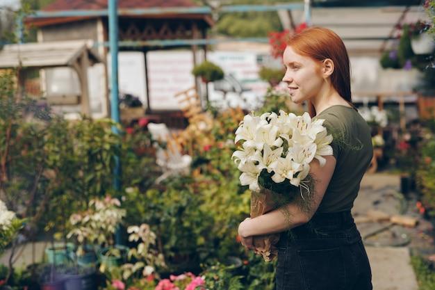 Sorridente bella ragazza rossa che tiene i gigli nel sacchetto di carta e guardandosi intorno, lei cresce fiori in serra