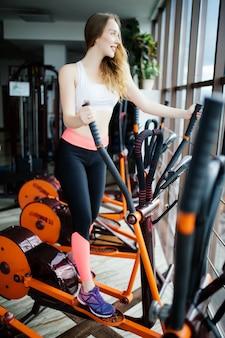 Sorridente bellezza fitness donna è impegnata in palestra sul simulatore. concetto di allenamento cardio, perdita di peso e uno stile di vita sano
