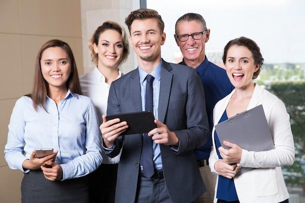 Sorridente business team in piedi in sala conferenze