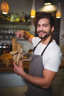Sorridente cameriere imballaggio croissant in sacco di carta a cafã ©