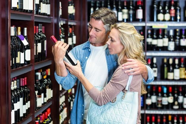 Sorridente coppia casual guardando la bottiglia di vino