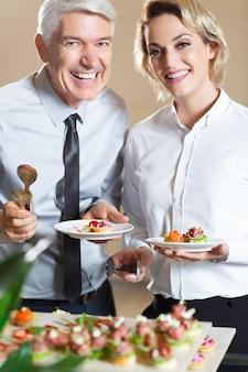 Sorridente coppia con spuntini in piedi a buffet