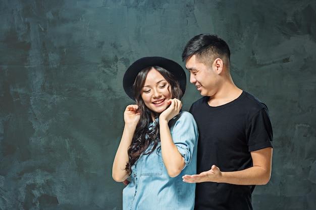 Sorridente coppia coreana su grigio