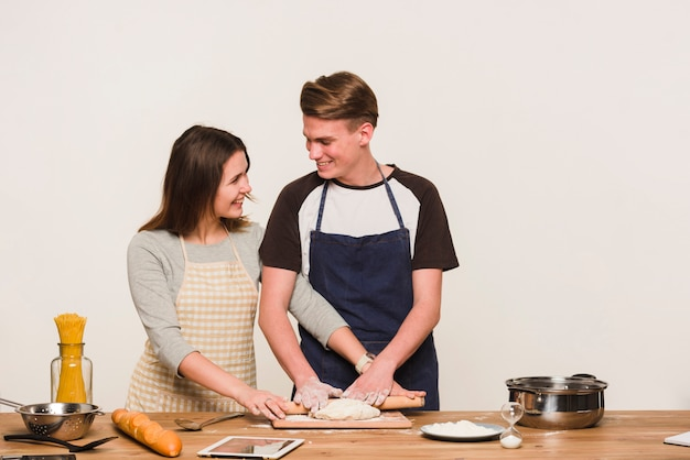 Sorridente coppia di rotolare la pasta insieme