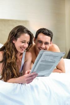 Sorridente coppia sdraiata a letto con un giornale