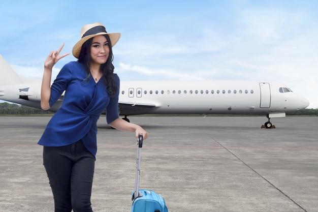 Sorridente donna asiatica con una valigia in piedi