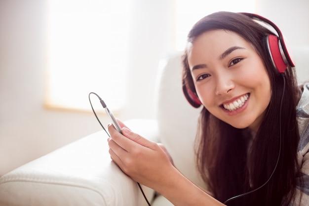 Sorridente donna asiatica sul divano ascoltando musica