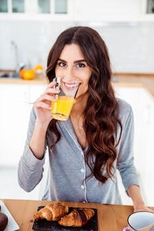Sorridente donna che beve il succo per la colazione