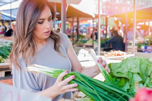 Sorridente donna con verdure al negozio di mercato. donna che sceglie verdure fresche nel mercato verde. ritratto di bella giovane donna che sceglie verdure a foglia verde