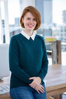 Sorridente donna d'affari hipster, in piedi nel suo ufficio con le braccia conserte
