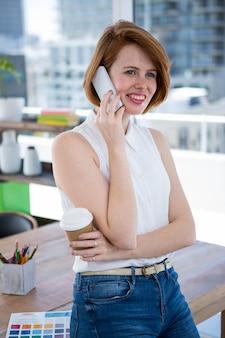 Sorridente donna d'affari hipster seduto alla sua scrivania, con in mano una tazza di caffè