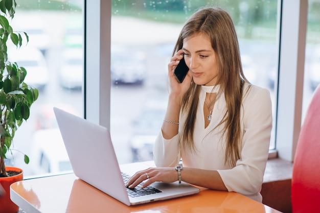 Sorridente donna elegante parla al telefono e lo schermo del suo computer