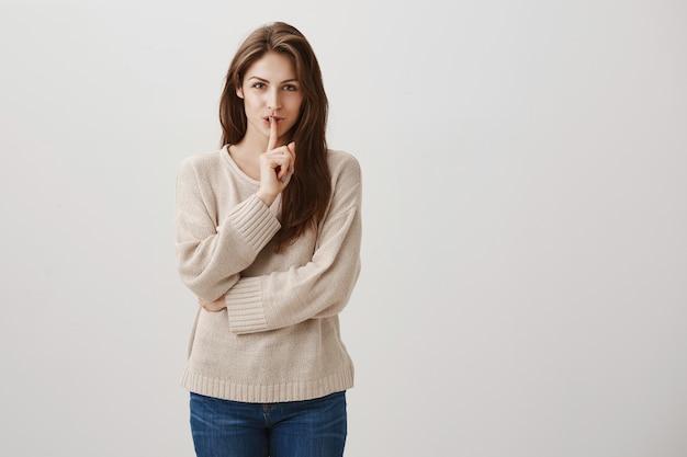 Sorridente donna felice che nasconde il segreto, fare il gesto di silenzio per tacere