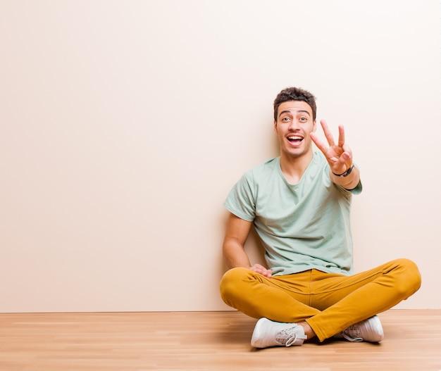 Sorridente e amichevole, mostrando il numero tre o il terzo con la mano in avanti, il conto alla rovescia