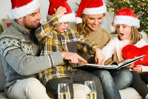 Sorridente famiglia con cappelli di babbo natale e guardando un album di foto