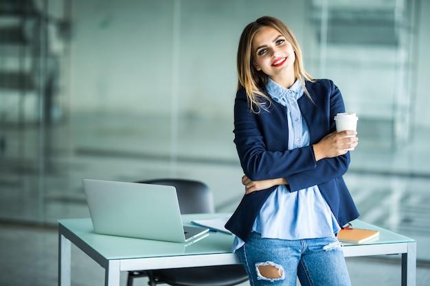 Sorridente fiduciosa giovane donna d'affari con i capelli ricci in piedi alla scrivania comune e guardando mentre beve il caffè in ufficio open space