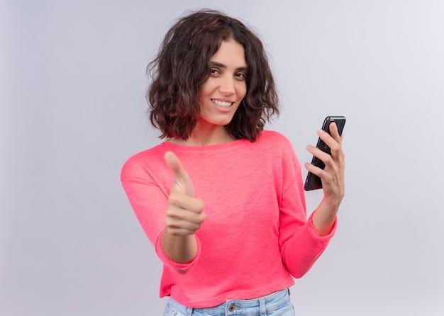 Sorridente giovane bella donna che tiene il telefono cellulare e che mostra il pollice in su sulla parete bianca isolata