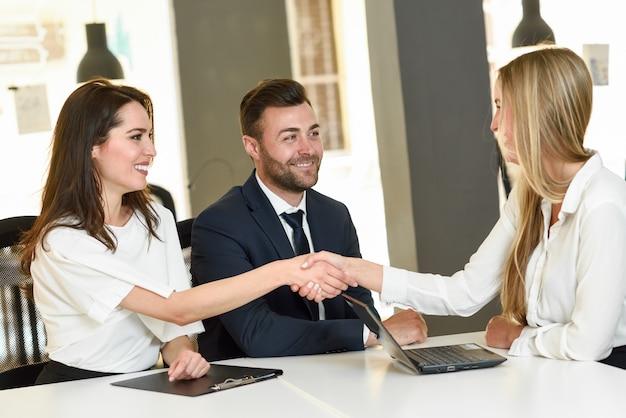 Sorridente giovane coppia si stringono la mano con un agente assicurativo